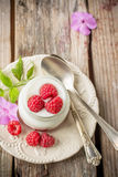 Natural yogurt with fresh raspberries and. Raspberry jam for breakfast in portion jars on a wooden background. selective Focus Stock Image