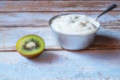 .Natural yogurt and kiwi fruit on wooden table stock photos