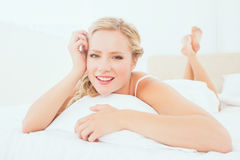 Natural young blonde lying on her bed smiling at camera Stock Photography