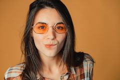 Natural young brunette girl with pimples biting lips on orange background. A studio portrait of a cute young brunette girl with pimples and glasses biting lips stock photos