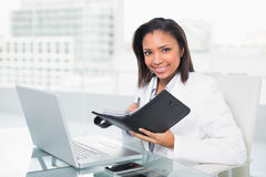 Natural young dark haired businesswoman filling her schedule Stock Images