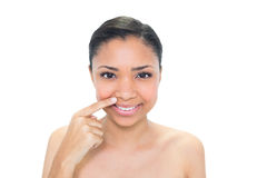 Natural young dark haired model pointing her nostril with her finger Stock Photography
