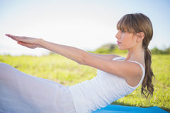 Natural young woman exercising. Outside doing core pilates exercise Stock Photography