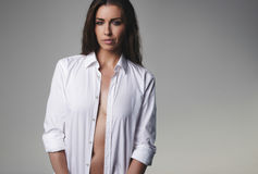 Natural young woman wearing an unbuttoned shirt. And looking at you. Sexy caucasian woman posing on grey background Stock Photo