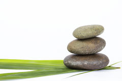 Natural zen stone on fresh green bamboo leaf Royalty Free Stock Image