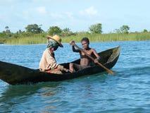 Naturales malgaches que cruzan el río en canoa fotos de archivo libres de regalías