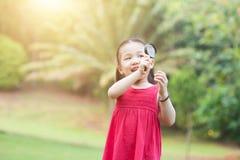 Naturaleza de exploración de la niña con el vidrio de la lupa en al aire libre fotografía de archivo