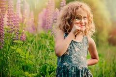 Naturaleza de exploración de la muchacha feliz del niño con la lupa en paseo del verano Imágenes de archivo libres de regalías