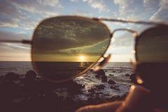 Naturaleza en la puesta del sol con la mano que sostiene vidrios, tono del vintage foto de archivo