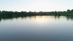 Naturaleza hermosa, lago limpio entre árboles verdes contra el cielo en la posluminiscencia almacen de metraje de vídeo