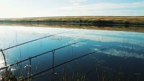 Naturaleza pintoresca hermosa de la mañana Las cañas de pescar se abandonan en la orilla del lago y son el esperar almacen de video