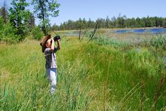 The Naturalist. Young boy with binoculars at lake Stock Photo