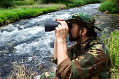 Bird watching in nature. The naturalist in military uniform with binoculars is on bird watching mission in nature at riverside Stock Photo