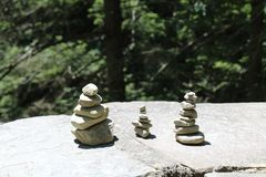 Naturally balanced stones sitting on a stone wall. Small stacked stones. Dark green pine trees in the background stock image