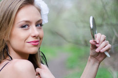 Naturally beautiful young blond woman in nature holding a mirror Stock Photography