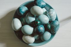 Naturally dyed Easter blue eggs, scattered on blue plate, on whi Stock Photos