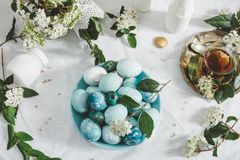 Naturally dyed Easter blue eggs, and tea cup. Urrounded by white flowers on the table with white tablecloth stock photography