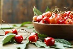 Naturalna świeża słodka wiśnia w talerzu z rozrzuconymi liśćmi wokoło zdjęcia stock