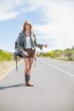 Naturalna blondynki kobieta pozuje podczas gdy hitchhiking Zdjęcia Royalty Free