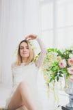 Naturalna młoda kobieta pozuje z kwiatami Zdjęcia Royalty Free