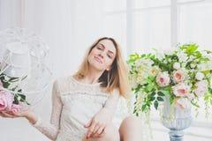 Naturalna młoda kobieta pozuje z kwiatami Fotografia Stock