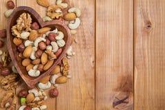 Naturalna odżywcza mieszanka różne dokrętki w drewnianym talerzu kierowy symbolu kształt na brązu drewnianym stole przy lewą stro zdjęcie royalty free