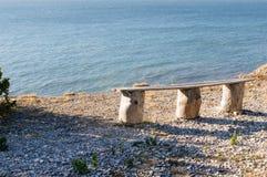 Naturalna odrewniała ławka na kamienistym dennym brzeg w Gotland Szwecja blisko Högklint, obraz stock