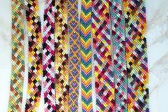 Naturalne bransoletki przyjaźń, kolorowe wyplatać przyjaźni bransoletki, śnieżny tło, tęcza barwią, w kratkę wzór Zdjęcie Royalty Free