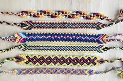 Naturalne bransoletki przyjaźń z rzędu, kolorowe wyplatać przyjaźni bransoletki, śnieżny tło, tęcza barwią, w kratkę wzór Zdjęcia Royalty Free