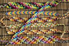 Naturalne bransoletki przyjaźń z rzędu, kolorowe wyplatać przyjaźni bransoletki, śnieżny tło, tęcza barwią, w kratkę wzór Zdjęcie Stock