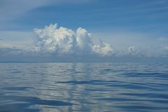 Naturalnego tła scena gradientowy niebieskie niebo horyzont i puszysta biel chmura nad głęboka błękitna woda morska pluskoczemy m Obraz Stock