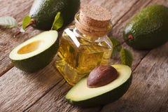 Naturalny avocado olej w butelce na drewnianym stołowym zakończeniu, horyzontalnym obrazy stock