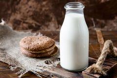 Naturalny cały mleko w butelce na starym drewnianym tle i Zdjęcie Stock