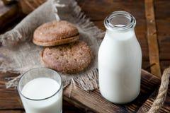 Naturalny cały mleko w butelce na starym drewnianym tle i Fotografia Stock