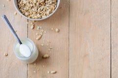 Naturalny jogurt w małym słoju i łyżce na górze słoju z pucharem owsa granola na drewnianym tle Obrazy Royalty Free