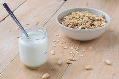 Naturalny jogurt w małym słoju z pucharem owsa granola na drewnianym tle Zdjęcie Stock