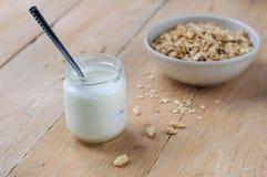 Naturalny jogurt w małym słoju z pucharem owsa granola na drewnianym tle Fotografia Royalty Free