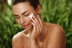 Naturalny pokojowy portret piękna dziewczyna z czystą skórą robi skincare z creme outdoors zdjęcia royalty free