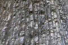 Naturalny siwieje płatowatą kamienistą góry ścianę z nierówną powierzchnią jako tło fotografia stock