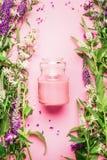 Naturalny ziołowy skóry opieki kosmetyka pojęcie Szklany słój z śmietanką, płukanka, świezi ziele lub kwiaty na różowym tle, odgó obrazy stock