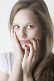 Naturaly beautiful woman touching her face with red nails hands. Close up portrait of young woman with shining eyes, fresh and clean skin face, healthy long Royalty Free Stock Photo