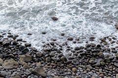 Naturbakgrund med kiselstenar på kusten av madeiraön Royaltyfri Fotografi