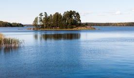 Naturbakgrund med kust- vassöar på horisonten och det glänsande sjövattnet Royaltyfria Foton