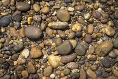 Naturbegreppsbakgrund av den naturliga stenen på flodstranden Arkivfoton