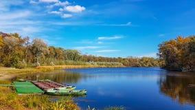 Nature湖与小船的秋天反射 风景树浇灌河背景 免版税库存图片