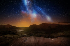 Mountain landscape over night sky or space. Nature and astronomy concept - mountain landscape over night sky or space with shooting stars background Royalty Free Stock Photos