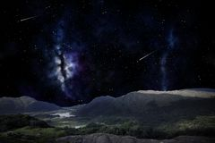 Mountain landscape over night sky or space. Nature and astronomy concept - mountain landscape over night sky or space with shooting stars background royalty free stock image