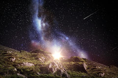 Rocky landscape over night sky or space. Nature and astronomy concept - rocky landscape over night sky or space with shooting stars background Stock Images