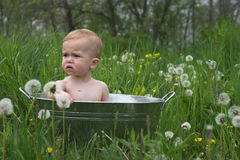 Nature Baby. Image of a cute baby sitting in a galvanized tub in a meadow Stock Photos