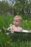 Nature Baby. Image of a cute baby sitting in a galvanized tub in a meadow Stock Photo